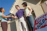 Couple shaking hands with estate agent outside their new home Stock Photo - Premium Royalty-Free, Artist: Andrew Kolb, Code: 693-06018027