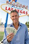 Mid-adult man holding notes in front of Welcome to Las Vegas sign, portrait Stock Photo - Premium Royalty-Free, Artist: Robert Harding Images, Code: 693-06018065