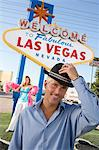 Portrait of mid-adult man in front of Welcome to Las Vegas sign, mid-adult woman in background. Stock Photo - Premium Royalty-Free, Artist: Kablonk! RM, Code: 693-06018068