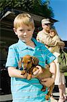 Boy (5-6) holding dog, outdoors, (portrait) Stock Photo - Premium Royalty-Free, Artist: Ikon Images, Code: 693-06018177