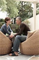 Smiling couple sitting on wicker chairs on patio Stock Photo - Premium Royalty-Freenull, Code: 693-06018456
