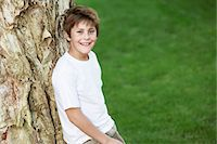 Boy leaning against tree, portrait Stock Photo - Premium Royalty-Freenull, Code: 693-06018467
