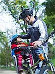 Girl (3-4) and father preparing to ride bicycle in park Stock Photo - Premium Royalty-Freenull, Code: 693-06018495