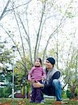 Girl (3-4) standing with father, squatting, in park Stock Photo - Premium Royalty-Free, Artist: CulturaRM, Code: 693-06018497
