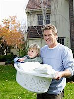 Father carrying boy (3-4) in laundry basket in yard Stock Photo - Premium Royalty-Freenull, Code: 693-06018498
