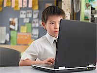 Elementary schoolboy using laptop in classroom Stock Photo - Premium Royalty-Freenull, Code: 693-06018553