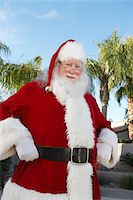 Smiling Santa Claus standing outside With Palm Trees Stock Photo - Premium Royalty-Freenull, Code: 693-06018592