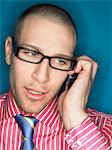 Man in glasses on cell phone, head and shoulders Stock Photo - Premium Royalty-Free, Artist: Blend Images, Code: 693-06018599