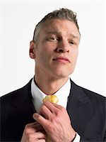 Man adjusting tie in studio, head and shoulders Stock Photo - Premium Royalty-Freenull, Code: 693-06018623