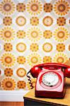 Old fashioned red telephone on table in front of flowery wallpaper Stock Photo - Premium Royalty-Free, Artist: iRepublic, Code: 693-06018930