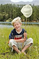 Boy (7-9) sitting in field, holding butterfly net, front view. Stock Photo - Premium Royalty-Freenull, Code: 693-06019155