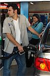 Woman watching gas station attendant pumping gas Stock Photo - Premium Royalty-Free, Artist: Simon Katzer, Code: 693-06019263