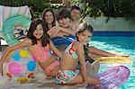 Family with two girls and boy with inflatable rafts sitting by swimming pool, portrait Stock Photo - Premium Royalty-Free, Artist: Peter Barrett, Code: 693-06019365