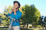 Senior woman fixing bicycle helmet Stock Photo - Premium Royalty-Free, Artist: ableimages, Code: 693-06019403