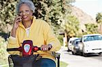 Senior woman on motor scooter on urban street, talking on mobile phone Stock Photo - Premium Royalty-Free, Artist: Blend Images, Code: 693-06019434