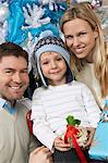 Couple with son (5-6) holding present in front of Christmas tree Stock Photo - Premium Royalty-Free, Artist: Andrew Kolb, Code: 693-06019512