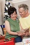 Senior couple looking at card over Christmas presents Stock Photo - Premium Royalty-Free, Artist: Jodi Pudge, Code: 693-06019524