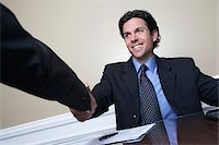 Business man shaking hands with colleague at desk in office Stock Photo - Premium Royalty-Freenull, Code: 693-06019595