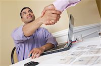 Two men shaking hands over desk with name tags Stock Photo - Premium Royalty-Freenull, Code: 693-06019615