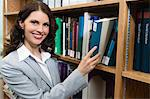 Portrait of woman reaching for book from bookshelf Stock Photo - Premium Royalty-Free, Artist: Blend Images, Code: 693-06019697