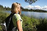 USA, Alaska, woman looking through binoculars at lake Stock Photo - Premium Royalty-Free, Artist: Blend Images, Code: 693-06019763
