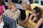 Teacher helping two students working in computer classroom Stock Photo - Premium Royalty-Freenull, Code: 693-06019889