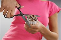 Woman cutting bundle of cigarettes, close-up Stock Photo - Premium Royalty-Freenull, Code: 693-06019984