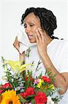Woman with allergy holding tissue, near flowers, studio shot Stock Photo - Premium Royalty-Freenull, Code: 693-06020012