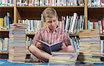 Boy sitting on the floor and reading book in library Stock Photo - Premium Royalty-Free, Artist: R. Ian Lloyd, Code: 693-06020471