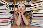 School girl sitting at desk with books in library Stock Photo - Premium Royalty-Free, Artist: CulturaRM, Code: 693-06020477
