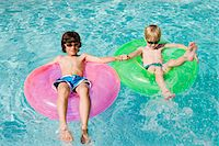 Boys on Float Tubes in Swimming Pool Stock Photo - Premium Royalty-Freenull, Code: 693-06020736