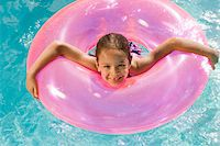 preteen swim - Girl Inside Pink Float Tube in Pool Stock Photo - Premium Royalty-Freenull, Code: 693-06020739