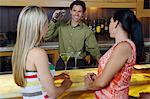 Bartender Mixing Drinks for Women at Bar Stock Photo - Premium Royalty-Freenull, Code: 693-06021221