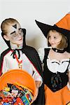 Girl and boy (7-9), wearing Halloween costumes, studio shot Stock Photo - Premium Royalty-Free, Artist: Raimund Linke, Code: 693-06021612