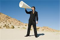 Businessman Using Megaphone in Desert Stock Photo - Premium Royalty-Freenull, Code: 693-06021778