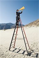 Businessman on Stepladder Using Megaphone in Desert Stock Photo - Premium Royalty-Freenull, Code: 693-06021781