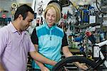 Bike shop assistant helps female cyclist Stock Photo - Premium Royalty-Free, Artist: Blend Images, Code: 693-06021909
