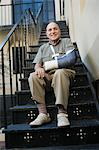 Man with broken arm sitting on stairs Stock Photo - Premium Royalty-Freenull, Code: 693-06021929
