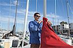 Young man securing sail of boat Stock Photo - Premium Royalty-Free, Artist: Science Faction, Code: 693-06022160