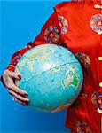 Woman in Chinese pajamas holding globe Stock Photo - Premium Royalty-Free, Artist: Blend Images, Code: 673-06025394