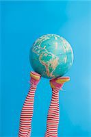 Legs in striped socks with colorful shoes holding globe Stock Photo - Premium Royalty-Freenull, Code: 673-06025425