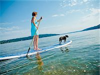 Woman on paddle board with dog Stock Photo - Premium Royalty-Freenull, Code: 673-06025478