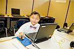Young boy seated at school laptop in computer lab Stock Photo - Premium Royalty-Free, Artist: Blend Images, Code: 673-06025532