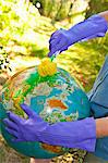 Woman wearing rubber gloves to scrub globe outdoors Stock Photo - Premium Royalty-Free, Artist: Uwe Umsttter, Code: 673-06025568