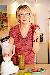 Woman making smoothie in kitchen blender Stock Photo - Premium Royalty-Free, Artist: Tim Hurst, Code: 673-06025709