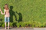 Girl making shadow on hedge Stock Photo - Premium Royalty-Free, Artist: Norbert Schäfer, Code: 632-06029320