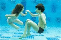 preteen swim - Brother and sister playing underwater in swimming pool Stock Photo - Premium Royalty-Freenull, Code: 632-06029363