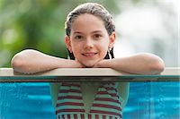 preteen swim - Girl in bikini leaning on edge of swimming pool, smiling, portrait Stock Photo - Premium Royalty-Freenull, Code: 632-06029438