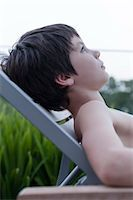Boy reclining on deckchair Stock Photo - Premium Royalty-Freenull, Code: 632-06029520