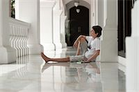 Boy sitting on floor of veranda daydreaming Stock Photo - Premium Royalty-Freenull, Code: 632-06029718